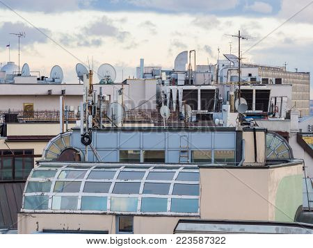 Many ventilation pipes, dish antenna, air-conditioners on the top of building. Roof with many technical equipment. Russia, Moscow.