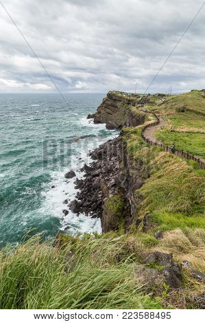 View of rugged landscape and coastal walkway next to the Songaksan Mountain on Jeju Island in South Korea.