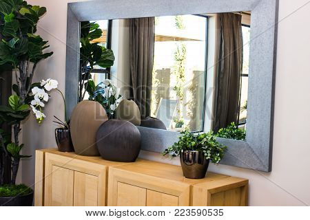 Wooden Hutch, Large Mirror, Plants And Jars In Modern Dining Room