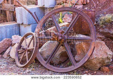 Large Vintage Iron Rusty Wheels And Ore Bucket Used For Mining Operations