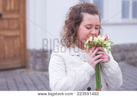 Beautiful portrait of curly woman holding red rose at the park.