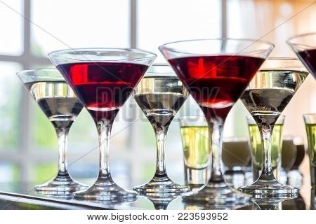 Several glasses of the famous Martini cocktail stand on a bar table.