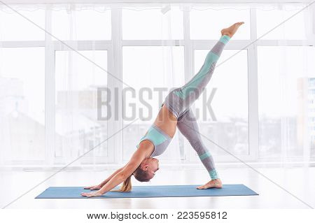 Beautiful young woman practices yoga asana eka pada Adho Mukha Shvanasana - One Leg Downward Dog pose at the bright yoga class with large windows