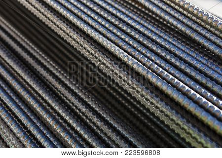 New metal bars in the storage warehouse. Metal rolling and metal structures. Stacked metal rods. Abstract background, soft focus and beautiful bokeh.