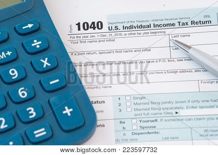 Federal Tax Form with Calculator and Pen