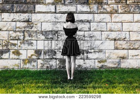 Young beautiful girl hugged her arms around her waist and stands face to the wall. The concept of loneliness and depression. Inner spiritual emptiness and sadness