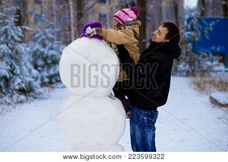 Happy father and little daughter sculpt a big real snowman, Happy family play in a winter park