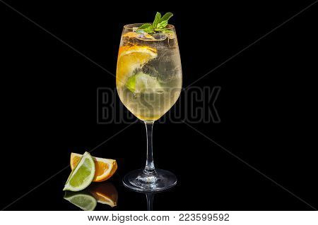 Alcoholic orange juice on a black background decorated with an orange slice and mint.