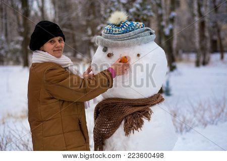 Happy senior woman sculpt a big real snowman in winter park