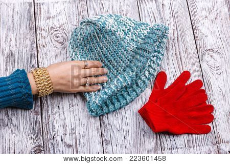 Reaching for her knit hat. A woman's hand is reaching for the wool knit hat y the red gloves.