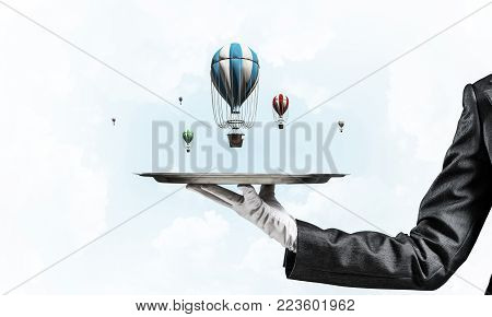 Closeup of waitress's hand in glove presenting flying aerostats on metal tray with blue cloudy skyscape on background. 3D rendering.