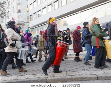 STOCKHOLM, SWEDEN - JAN 21, 2018: Girls play drum in the Womens March, a worldwide protest for women's rights in central Stockholm, Norrmalmstorg, Sweden, January 21, 2018