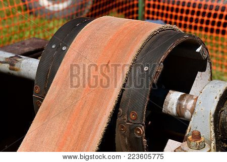 A huge leather belt is attached to a pulley and crankshaft in the process of transferring transfer energy