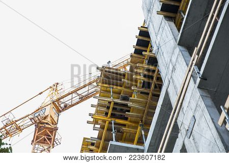 a building crane, stands near an unfinished building, a view from below. Construction crane