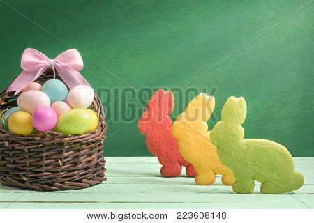 Multicolor Easter eggs and bunny shaped cookies - Easter banner design with a wicker basket full of colorful painted eggs, with a ribbon bow and three bunny shaped cookies, on a green background.