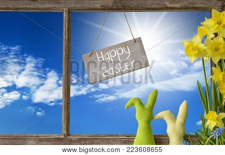 Sign With English Text Happy Easter. Window Frame With View To Beautiful Sunny Blue Sky. Easter Bunny And Narcissus In Front