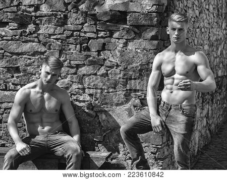 Two brothers twin muscular bodybuilders with bare chest strong young men sexy models in jeans pose outside on mural background