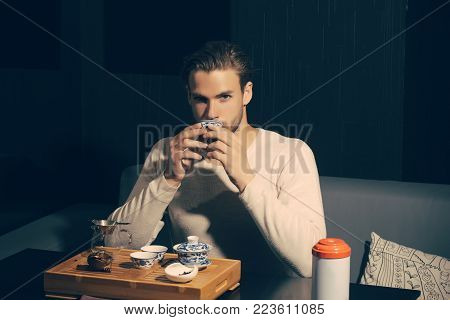 Brew tea concept. Man drink tea on sofa in cafe. Relaxation, lounge, relax. Tea party, ceremony, time. Beverage, food, cuisine.