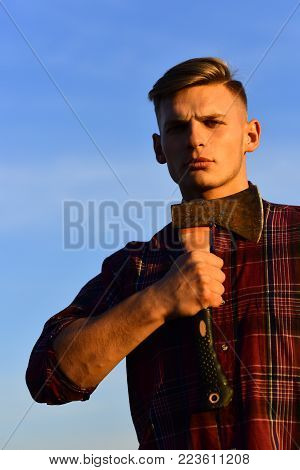 Man lumberjack shaving with axe in sunset. Wanderlust, hiking and travel. summer holiday and travel. man with axe, camping, hiking, suicide. lumberjack guy with ax on blue sky background, camping.