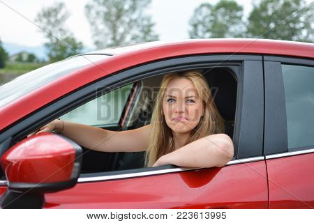 Young, attractive blonde girl in new red car, with strange facial expression, mocking at somebody