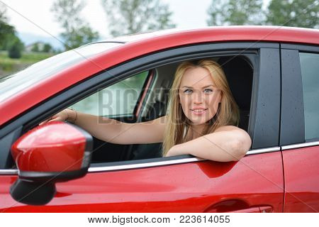 Young, attractive blonde girl in new red car, smiling and looking satisfied with her life