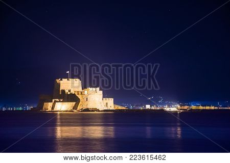 Illuminated old town of Nafplion in Greece with tiled roofs, small port, bourtzi castle, Palamidi fortress at night.