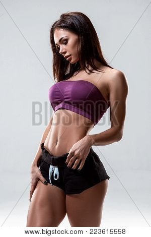 cropped close up body of fit woman wearing shorts and sport top showing slim beautiful stomach and abs in diet fitness and healthy lifestyle concept isolated on grey background. Brunette sexy fitness girl in sport wear with perfect body posing in the stud