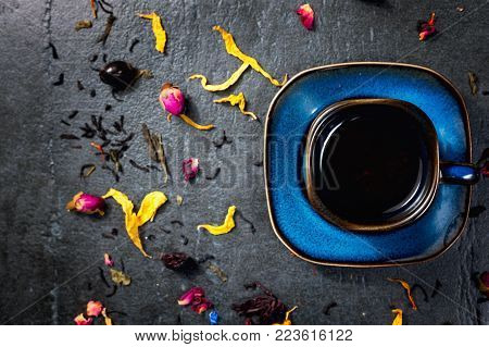 Cup of tea with herbs and flowers on stone background top view