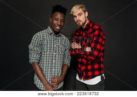 Studio shot of two stylish young men having fun. Handsome bearded hipster in a shirt in a cage standing next to his African-American friend against a dark background. International friendship concept.