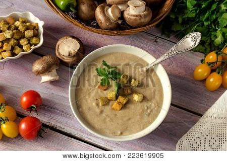 Fresh, mushroom soup puree in a bowl, crouton and vegetables in a wicker basket on a wooden table close-up
