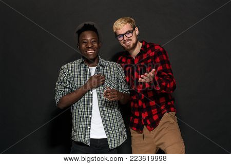 Studio shot of two stylish young men having fun. Handsome bearded hipster in a shirt in a cage standing next to his African-American friend in hat against a dark background. International friendship concept.