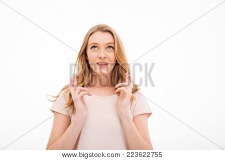 Image of cute young hopeful lady standing isolated over white background. Looking aside.