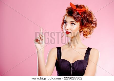 Portrait of a funny emotional young woman with curly foxy hair and a red bow on hair. Pin-up style. Bright make-up. Beauty, cosmetics.