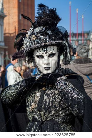 VENICE, ITALY - FEBRUARY 18, 2017: Portrait of unidentified woman in black costume, gloves, hat and white mask on San Marco Square during famous traditional Carnival taking place each year in Venice.