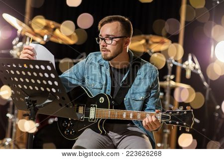 music, people, musical instruments and entertainment concept - male guitarist playing electric guitar with stand at studio rehearsal over lights