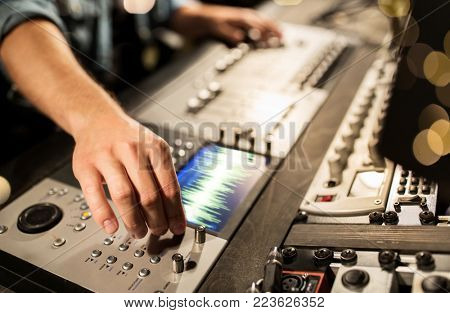 music, technology, people and equipment concept - man using mixing console in sound recording studio over lights