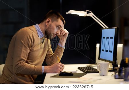 software development, business, deadline and technology concept - web designer with notepad and user interface mockup on computer screen working at night office