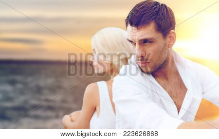 people and relationships concept - unhappy couple over sea background