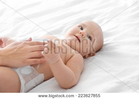 Woman applying body cream on her baby indoors