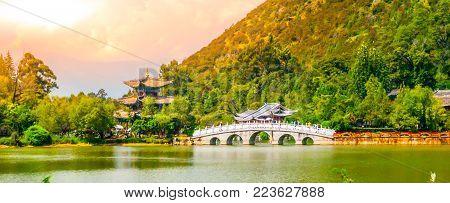 Suocui Bridge over Black Dragon Pool at Moon Embracing Pavilion in Jade Spring Park, Lijiang, China.