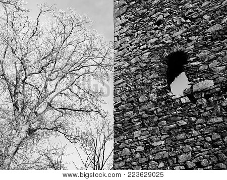 Construction detail of wall with window of old historical castle or ruin. Vintage architecture. Black and white image.