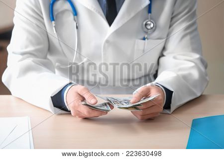 Doctor with money at table. Corruption concept