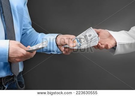 Doctor getting money from man on dark background. Corruption concept
