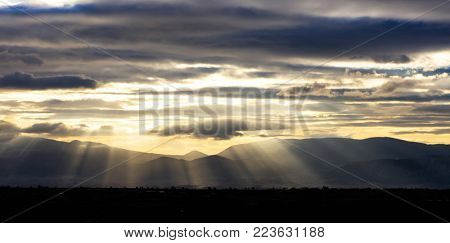 Storm clouds, colorful, heavy and sky backdrop. Sunbeams through the cloudscape, at sunset. Panoramic view