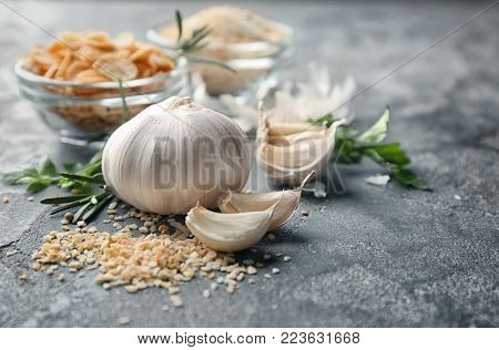 Ripe garlic and granules on grey background