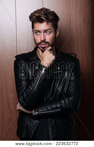 man fashion in leather jacket, wooden background