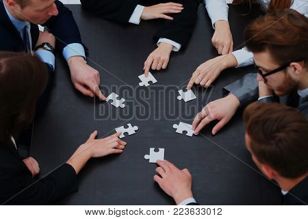 business team solving puzzle together.