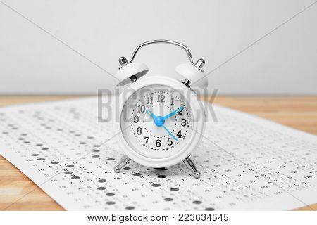 Alarm clock and test sheet on table, closeup. Preparation for exam