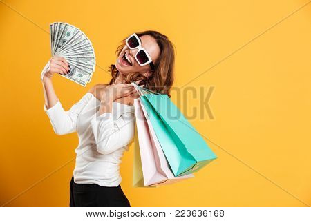Image of happy young woman standing isolated over yellow background holding shopping bags and money. Looking camera.