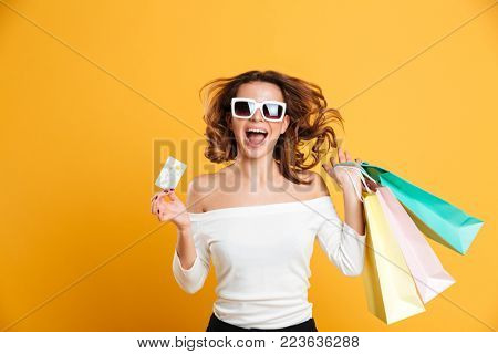 Image of cheerful young woman standing isolated over yellow background holding shopping bags and credit card. Looking camera.